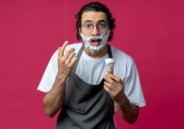 Jovem barbeiro caucasiano impressionado usando óculos e faixa de cabelo ondulado em uniforme segurando o pincel de barbear, mantendo as mãos no ar com creme de barbear colocado em sua barba isolada no fundo carmesim