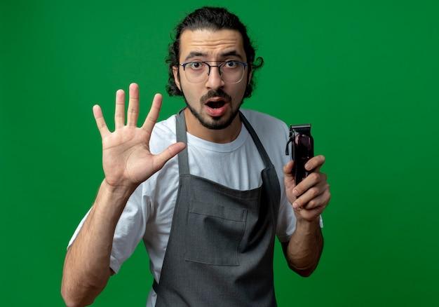 Jovem barbeiro caucasiano impressionado usando uniforme e óculos, segurando uma máquina de cortar cabelo e mostrando cinco com a mão isolada no fundo verde com espaço de cópia