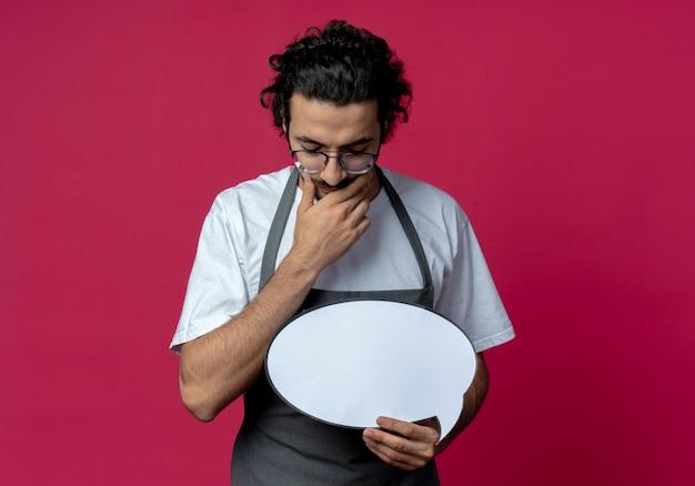 Jovem barbeiro caucasiano pensativo usando óculos e faixa de cabelo ondulado em uniforme segurando a bolha do bate-papo, colocando a mão no queixo, olhando para baixo, isolado no fundo carmesim com espaço de cópia