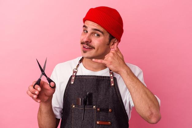 Jovem barbeiro caucasiano segurando uma tesoura isolada no fundo rosa, mostrando um gesto de chamada de telefone móvel com os dedos.