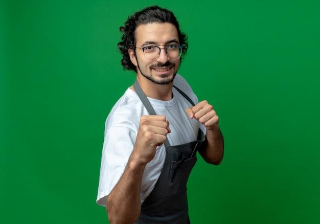 Jovem barbeiro caucasiano sorridente usando óculos e faixa de cabelo ondulado de uniforme, fazendo gesto de boxe para a câmera isolada em um fundo verde com espaço de cópia