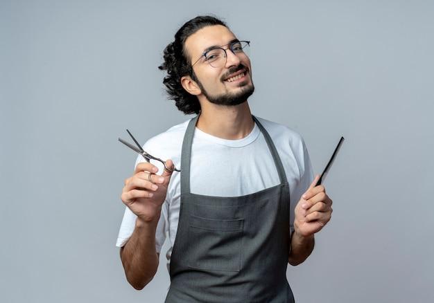 Jovem barbeiro caucasiano sorridente, usando óculos e faixa de cabelo ondulado de uniforme, segurando uma tesoura e um pente isolado no fundo branco com espaço de cópia