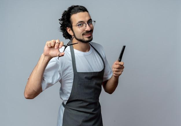 Jovem barbeiro caucasiano sorridente usando óculos e faixa de cabelo ondulado de uniforme segurando uma tesoura e um pente isolado no fundo branco com espaço de cópia