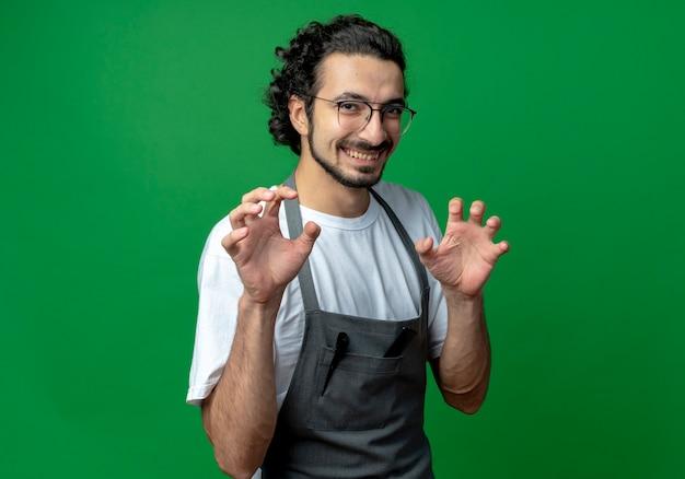 Jovem barbeiro caucasiano sorridente usando óculos e faixa de cabelo ondulado em uniforme fazendo gesto de patas de tigre isolado em um fundo verde com espaço de cópia