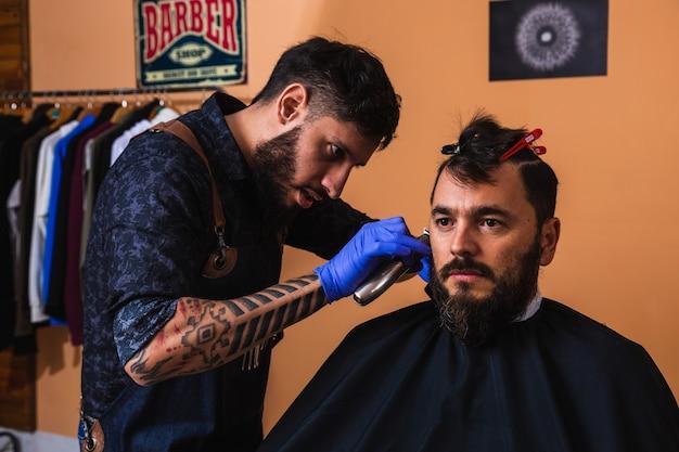 Jovem barbeiro com barba e tatuagens cortando a barba de um cliente - jovem barbeiro cortando a barba de um jovem bonito.