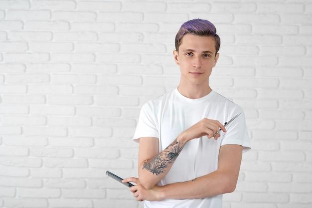 Jovem barbeiro com penteado elegante posando com tesoura e pente de plástico.