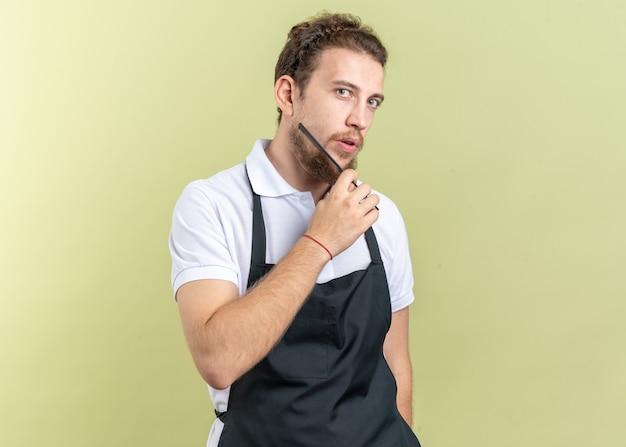 Jovem barbeiro confiante vestindo uniforme, penteando a barba com um pente isolado na parede verde oliva