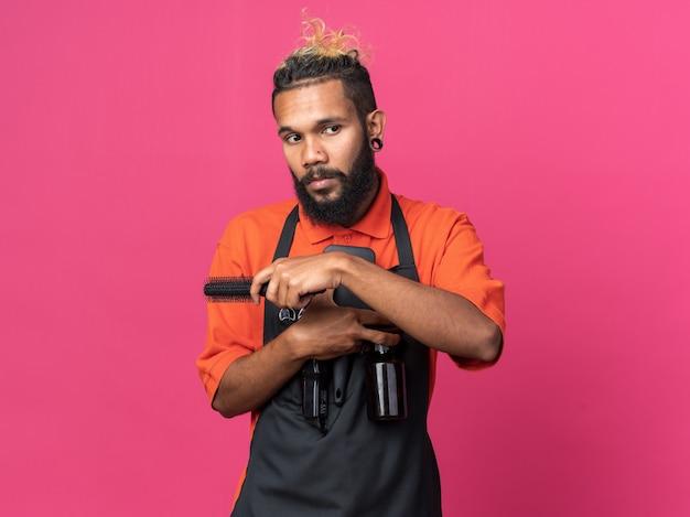 Jovem barbeiro confiante vestindo uniforme segurando pentes e spray de cabelo, olhando para o lado isolado na parede rosa com espaço de cópia