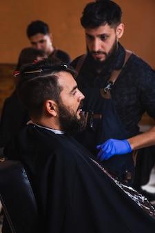 Jovem barbeiro cortando a barba de um jovem bonito - barbeiro cortando o cabelo de seu cliente na barbearia.