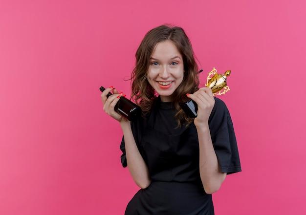 Jovem barbeiro eslavo feminino vestindo uniforme, segurando o copo do vencedor e o frasco de spray isolado em um fundo rosa com espaço de cópia
