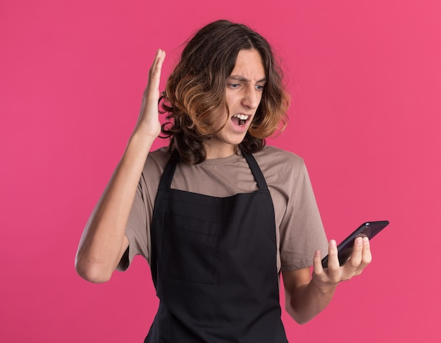 Jovem barbeiro furioso usando uniforme, segurando e olhando para o celular, mantendo as mãos no ar
