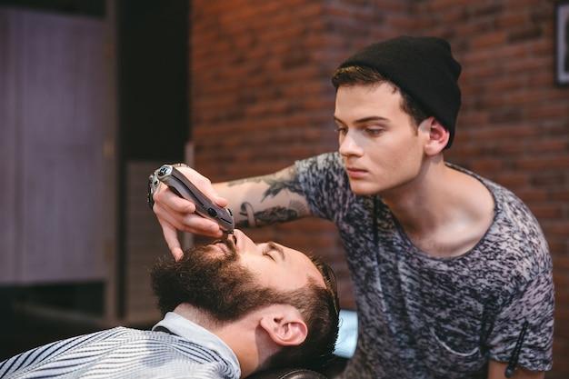 Jovem barbeiro habilidoso e concentrado aparando a barba de um jovem bonito na barbearia