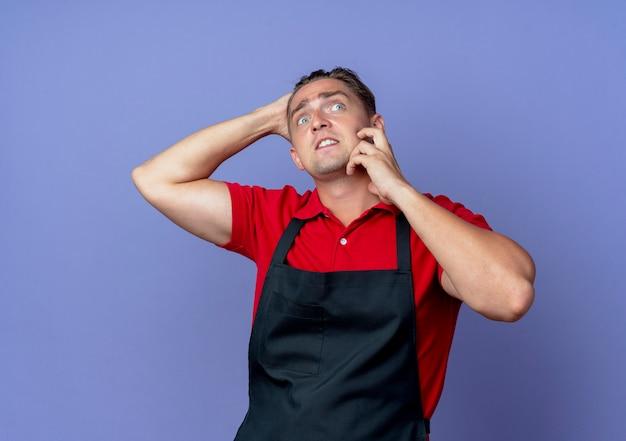 Jovem barbeiro loira ansiosa de uniforme coloca a mão no rosto, segurando a cabeça para trás, isolada no espaço violeta com espaço de cópia