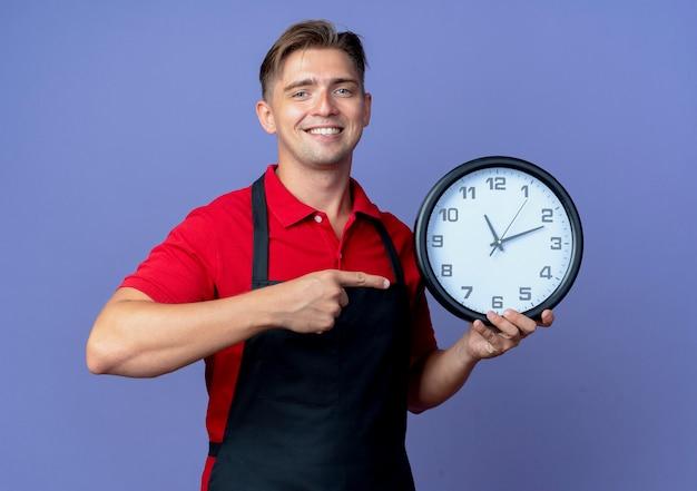 Jovem barbeiro loira sorridente de uniforme segura e aponta para o relógio isolado no espaço violeta com espaço de cópia