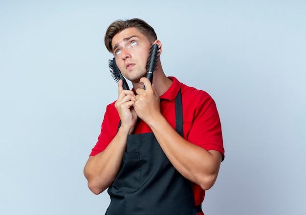 Jovem barbeiro loiro de uniforme coloca pentes de cabelo no rosto, olhando para cima