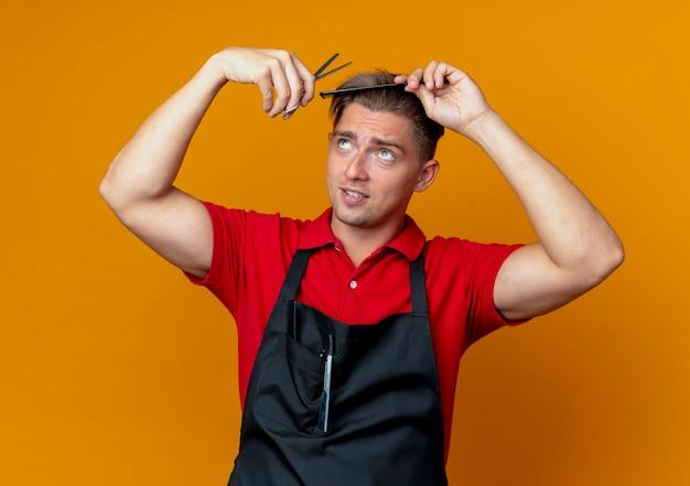 Jovem barbeiro loiro de uniforme tentando cortar o cabelo com um pente e uma tesoura olhando para cima