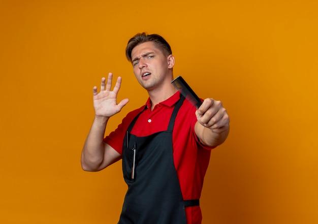 Jovem barbeiro loiro irritado de uniforme segurando um pente estendendo as mãos isoladas em um fundo laranja com espaço de cópia