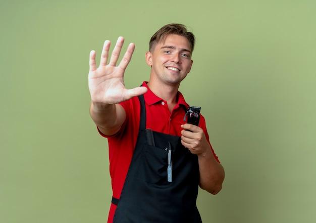 Jovem barbeiro loiro sorridente de uniforme gesticula cinco e segura o aparador de cabelo isolado no espaço verde oliva com espaço de cópia