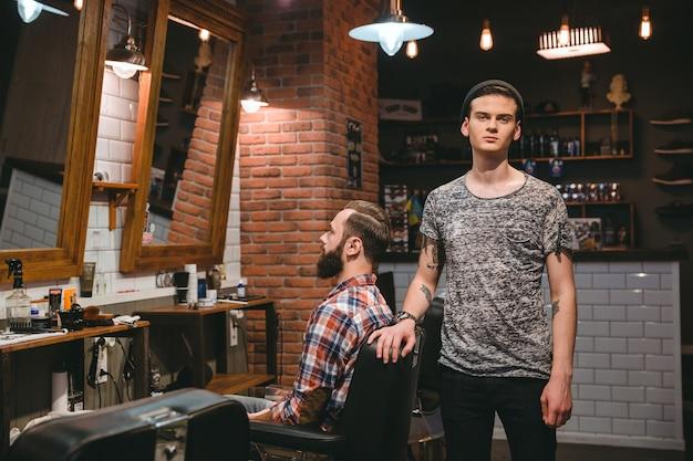 Jovem barbeiro moderno em seu local de trabalho com cliente em salão de cabeleireiro