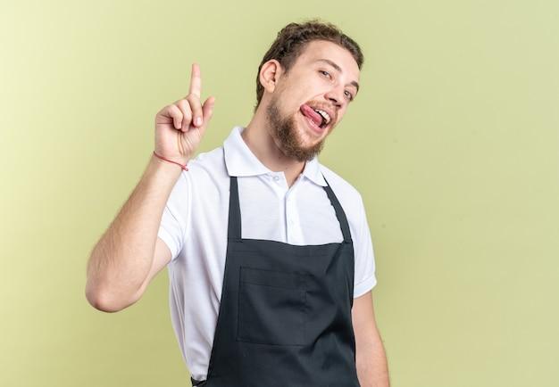 Jovem barbeiro satisfeito usando uniformes de pontas e mostrando a língua isolada na parede verde oliva
