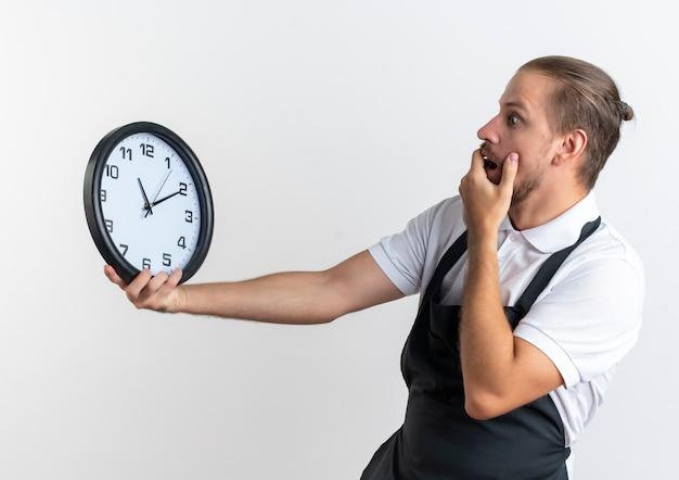 Jovem barbeiro surpreso e bonito vestindo uniforme segurando e olhando para o relógio colocando a mão na boca isolada na parede branca