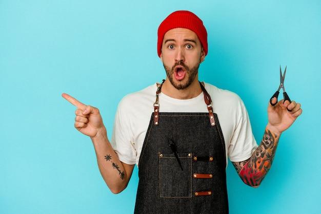 Jovem barbeiro tatuado isolado em um fundo azul apontando para o lado