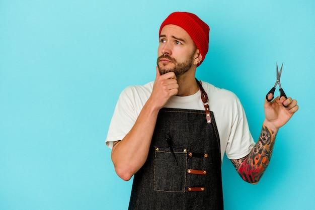 Jovem barbeiro tatuado isolado em um fundo azul, olhando de soslaio com expressão duvidosa e cética.