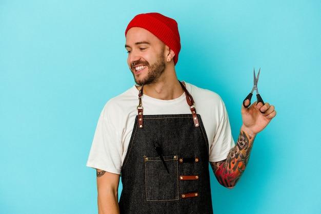Jovem barbeiro tatuado isolado em um fundo azul parece de lado sorrindo, alegre e agradável.