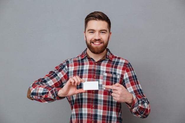 Jovem barbudo alegre com cartão em branco