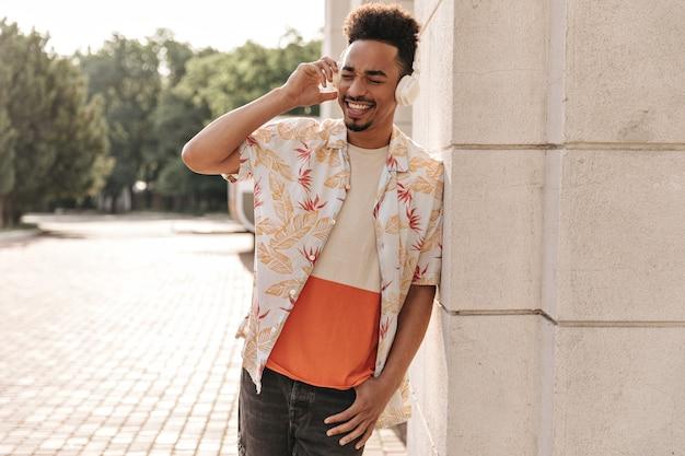 Jovem barbudo alegre, com uma camiseta colorida e uma camisa floral, se inclina na parede e ouve música em fones de ouvido do lado de fora