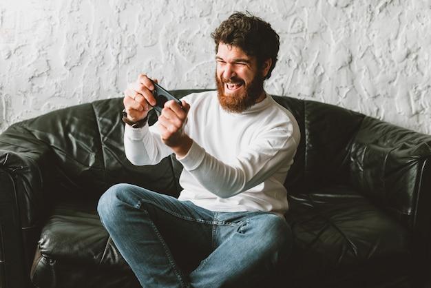 Jovem barbudo alegre jogando jogos no smartphone enquanto está sentado no sofá