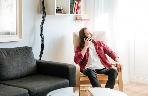 Jovem barbudo alegre sentado e falando no celular na poltrona em casa