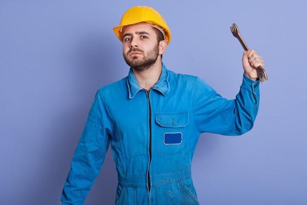 Jovem barbudo alegre usando capacete amarelo, segurando a ferramenta chave na mão e olhando diretamente para a câmera, olhando com raiva, quer bater em alguém com seu instrumento. conceito de emoções de pessoas.