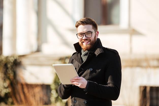 Jovem barbudo alegre usando computador tablet ao ar livre