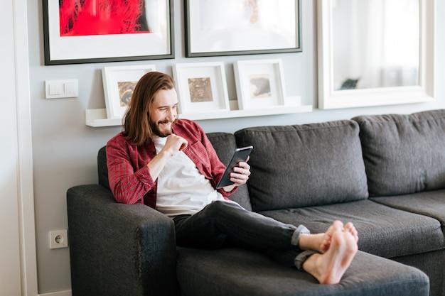 Jovem barbudo alegre usando tablet no sofá em casa