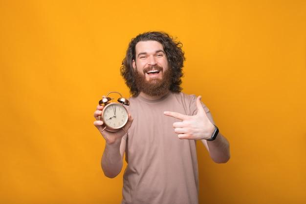 Jovem barbudo animado com cabelo comprido apontando para o despertador sobre o amarelo
