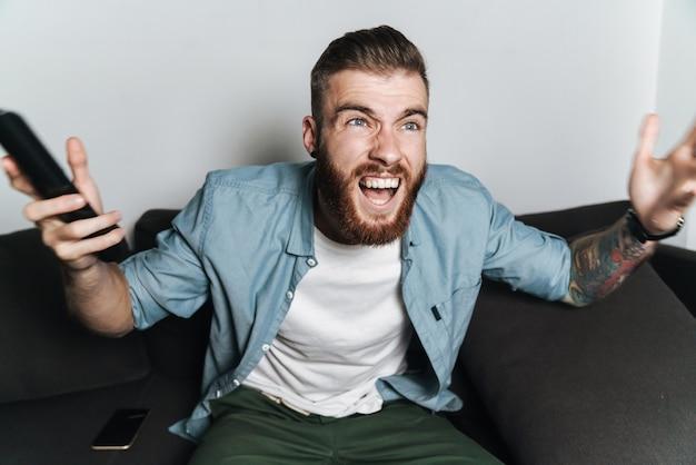 Jovem barbudo animado e atraente relaxando no sofá em casa, assistindo tv, gritando