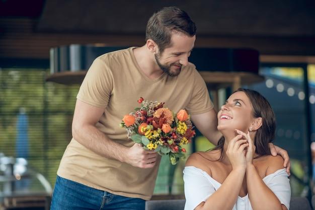 Jovem barbudo apaixonado com flores em pé perto de uma mulher feliz em um café