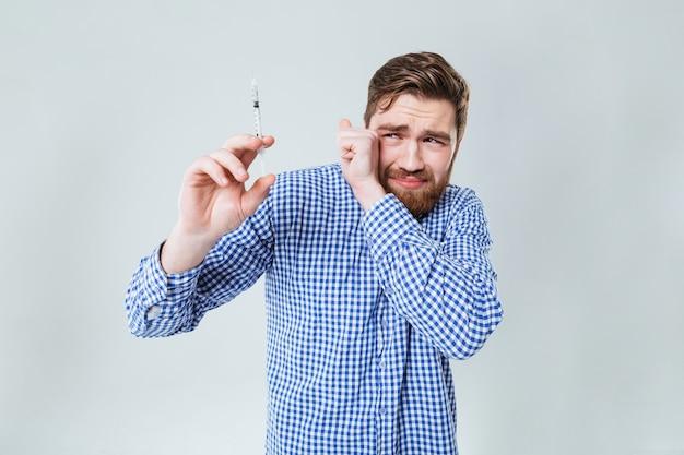Jovem barbudo assustado segurando uma seringa sobre uma parede branca