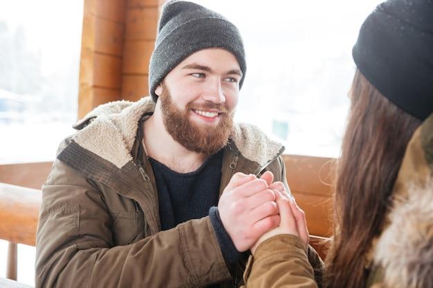 Jovem barbudo atraente e alegre, segurando as mãos da namorada, sentado ao ar livre no inverno