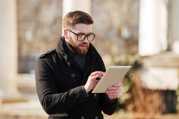 Jovem barbudo atraente usando computador tablet ao ar livre