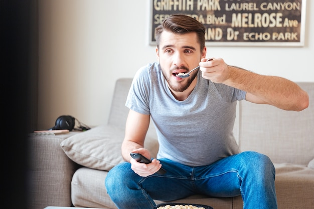 Jovem barbudo bonito com controle remoto sentado no sofá e comendo comida