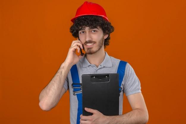 Jovem barbudo bonito construtor vestindo uniforme de construção e capacete de segurança segurando a área de transferência, falando no telefone móvel, sorrindo sobre parede laranja isolada
