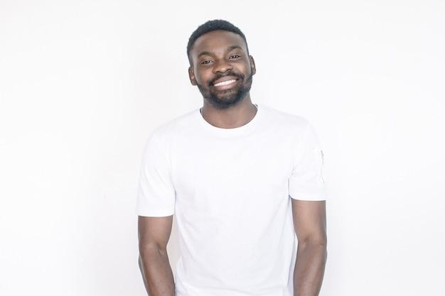 Jovem barbudo bonito, de pele escura, rindo alto de um meme engraçado que encontrou na internet, sorrindo amplamente, mostrando os dentes retos e brancos. expressões faciais humanas positivas e emoções