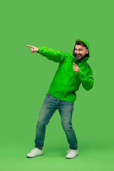 Jovem barbudo bonito isolado em verde