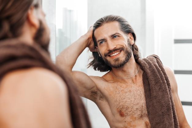 Jovem barbudo bonito olhando no espelho após o banho