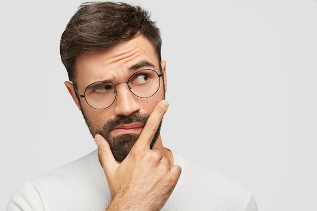 Jovem barbudo bonito segura o queixo e olha pensativo para o lado, levanta as sobrancelhas e pondera sobre algo