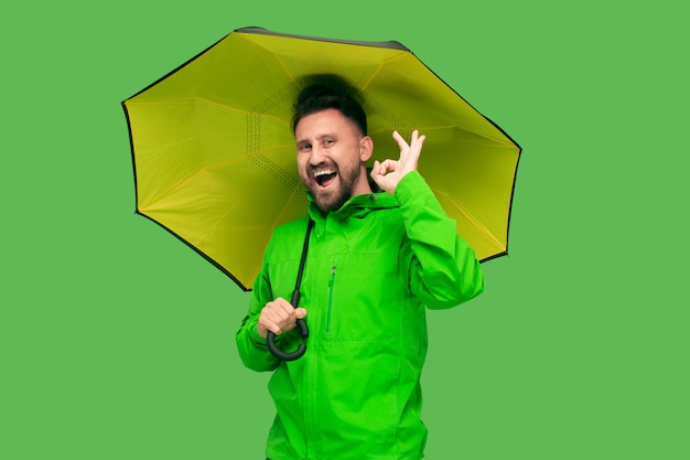 Jovem barbudo bonito segurando guarda-chuva