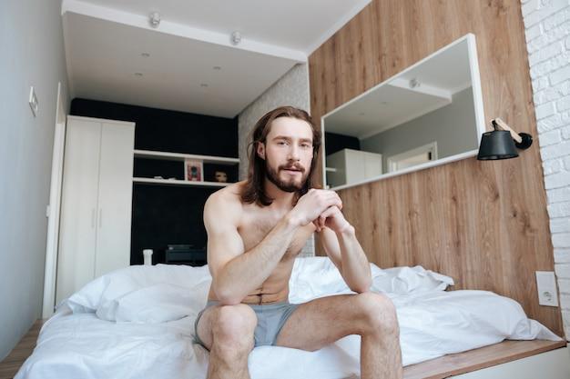 Jovem barbudo bonito sentado na cama