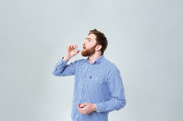 Jovem barbudo bonito tomando pílulas do frasco na parede branca